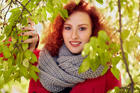 Redhead woman outdoor among leaves