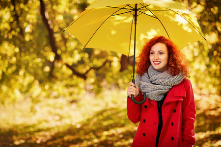 Ginger girl with umbrella in park in autumn