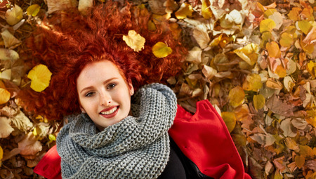 Ginger woman lying on leaves in park in autumn, top view Banque d'images