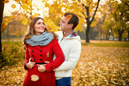 Nice young people in love embraced in park in autumn