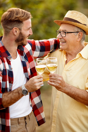 satisfied father and son tasting wine in vineyard - grape harvest