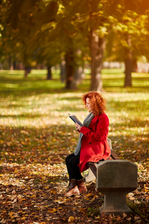 Curly redhead woman read book in park in autumn