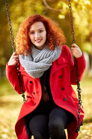 Red haired curly woman on a swing in park in autumn