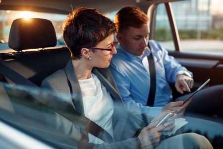 Conversation de deux collègues d'affaires dans la voiture de conduite
