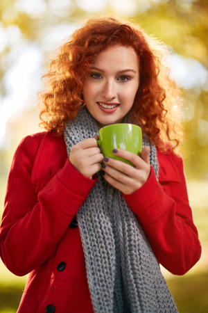 Red hair girl with cup of coffee in autumn