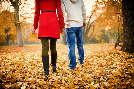 Young couple holding hands while walking in park in autumn