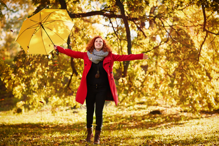 Cheerful redhead woman enjoying in park in autumn Banque d'images