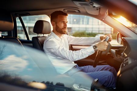 Young success businessman driving car