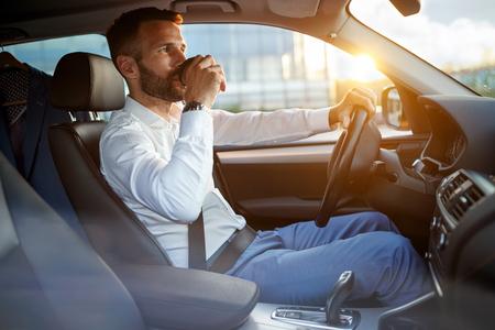 chef d'entreprise conduisant une voiture tout en buvant une tasse de café