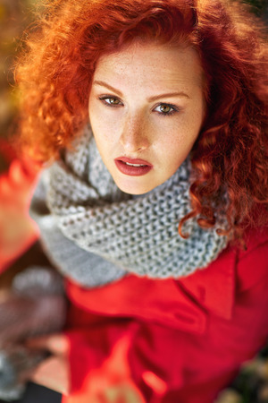 Curly redhead woman in autumn