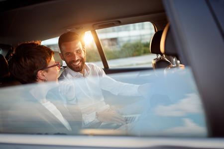 Des gens d'affaires souriants travaillant dans le siège arrière de la voiture