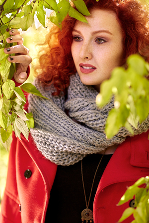 Curly red hair female in nature among trees in autumn