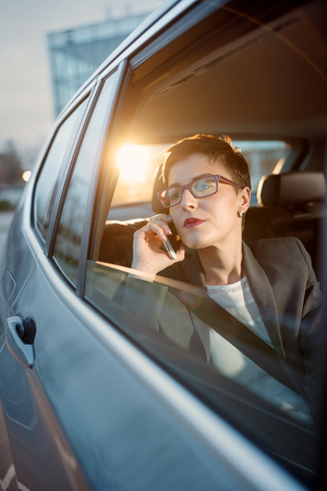 young business woman is driving in a car and use smartphone