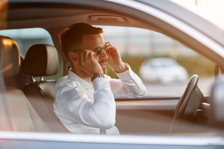 Homme d'affaires confiant portant des lunettes de soleil tout en conduisant une voiture Banque d'images