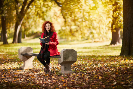 Curly redhead young female reading book in park in autumn