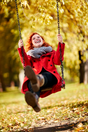 Curly ginger cheerful girl swinging on swing in park in autumn