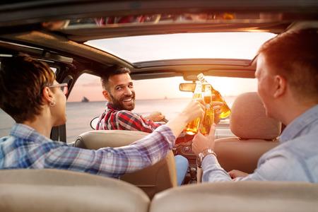 Les jeunes amis jouissent d'un voyage dans la voiture