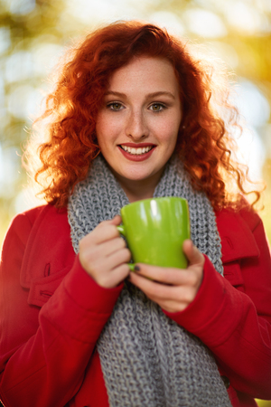 Cute ginger girl with green cup in nature Stock Photo