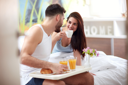 happy couple have romantic breakfast in bed