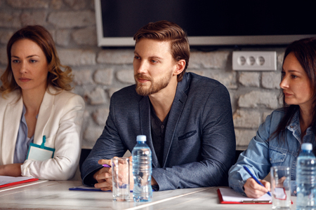 Serious man with two female colleagues in commission for employment in company Фото со стока