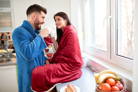 Beautiful couple in love drinking coffee in kitchen Фото со стока