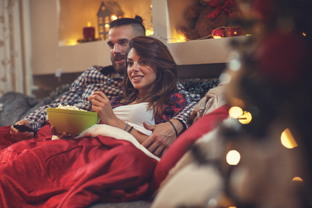 Jonge man en vrouw in bed die op TV letten en pop graan eten