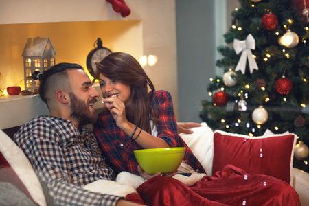 Femme nourrit son mari avec des vapeurs dans le lit à la veille de noël Banque d'images - 87287266