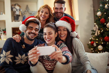 Young happy people making Christmas selfie