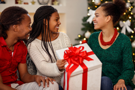 Afro-American cheerful smiling family with gift for Christmas celebration Stock Photo