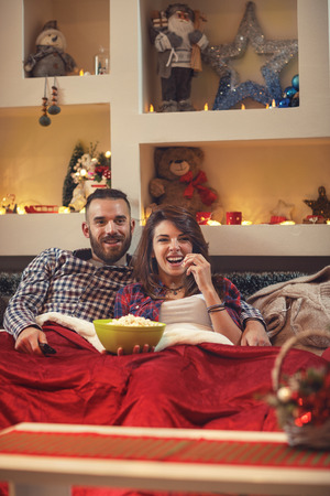 Young pair in bed in hug eating popcorn while watching movie on tv