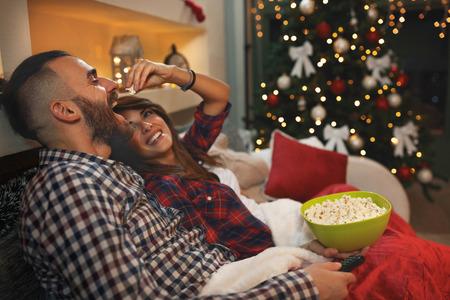 Pareja de enamorados en la víspera de Navidad disfruta con palomitas de maíz mientras ve la televisión