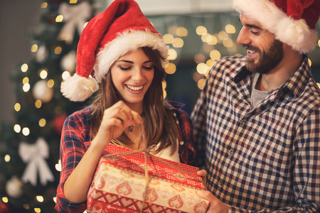 Cheerful man and woman opens Christmas gift Foto de archivo
