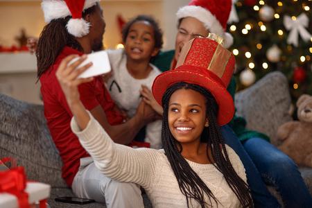 Mignonne petite fille afro américaine prenant selfie sur Noël Banque d'images - 87714304