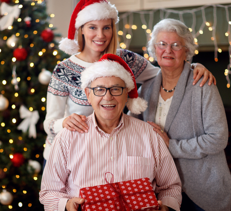 family, holidays, generation, Christmas and people concept – smiling daughter with elderly parents Stock Photo