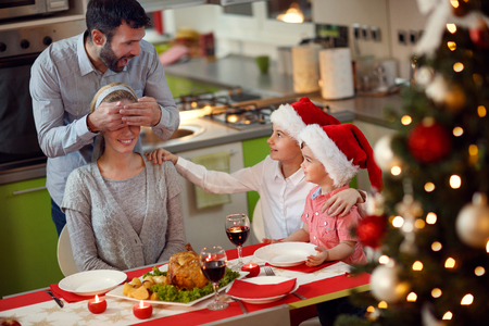 smiling father and children surprises mother with family Christmas dinner