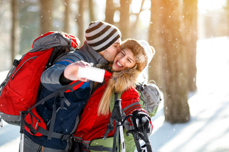 skiers: Young skiers kissing while making selfie in forest