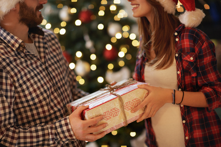 Christmas gift in box in couples hands, concept