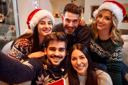group of smiling friends with sparklers enjoying in party on Christmas day