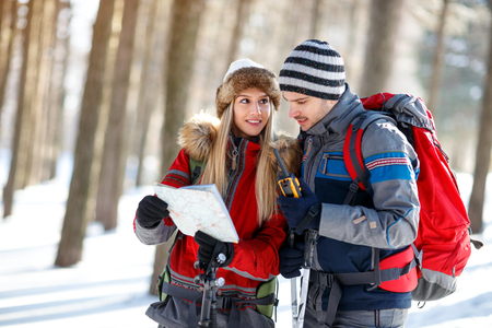 Young couple of hikers orienting themselves with map in forest