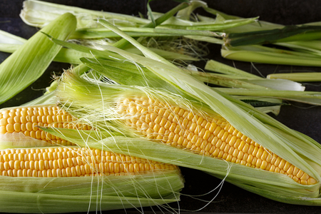 Fresh corn on black background, close-up Imagens