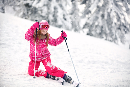 Pretty  girl on ski terrain practice to raise from snowy terrain