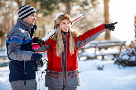 ski walking: Smiling girl on skiing shows something to his partner