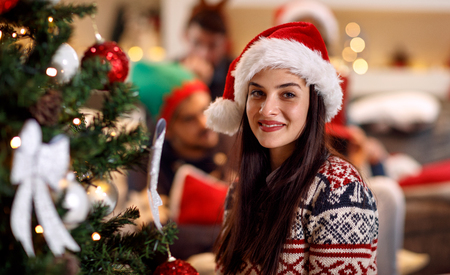 holidays, winter and people concept - happy young woman in Santa hat by Christmas tree at home Stockfoto
