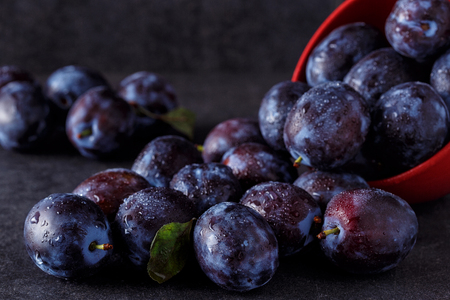 Fresh ripe plums over dark table background close up