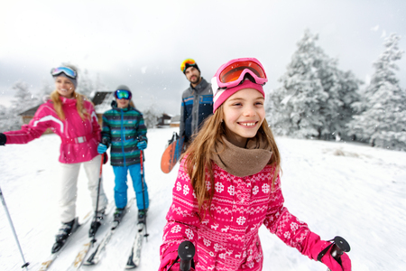 Cute girl skier skiing with family on mountain