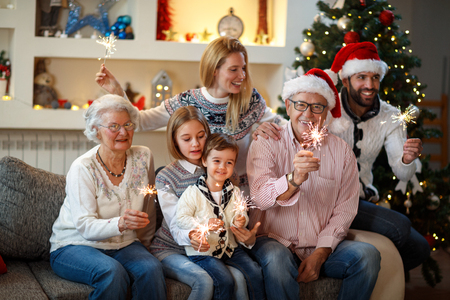 Grandparents with children holding Christmas sparkles in hands