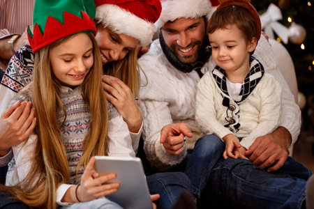 Children with parents looking something interesting on tablet Banque d'images
