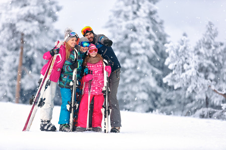 Family together skiing on snowy mountain and looking something in distance Banque d'images