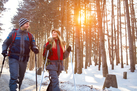 Love couple hiking in forest on winter