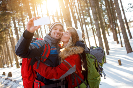 Girl kiss her boyfriend while taking selfie in snowy forest